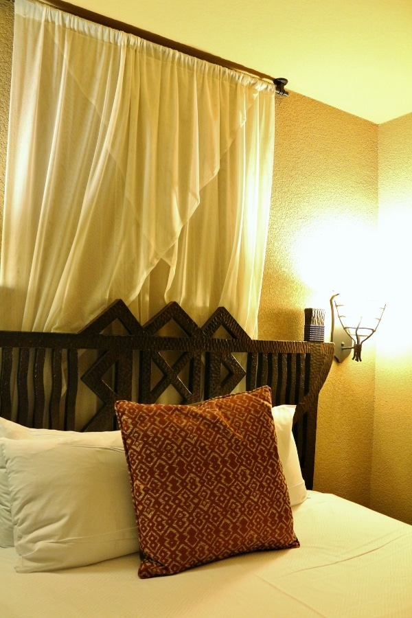 an ornate wooden headboard over a hotel bed