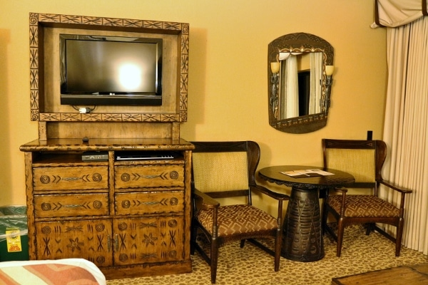a television, dresser, table and chairs inside a hotel room