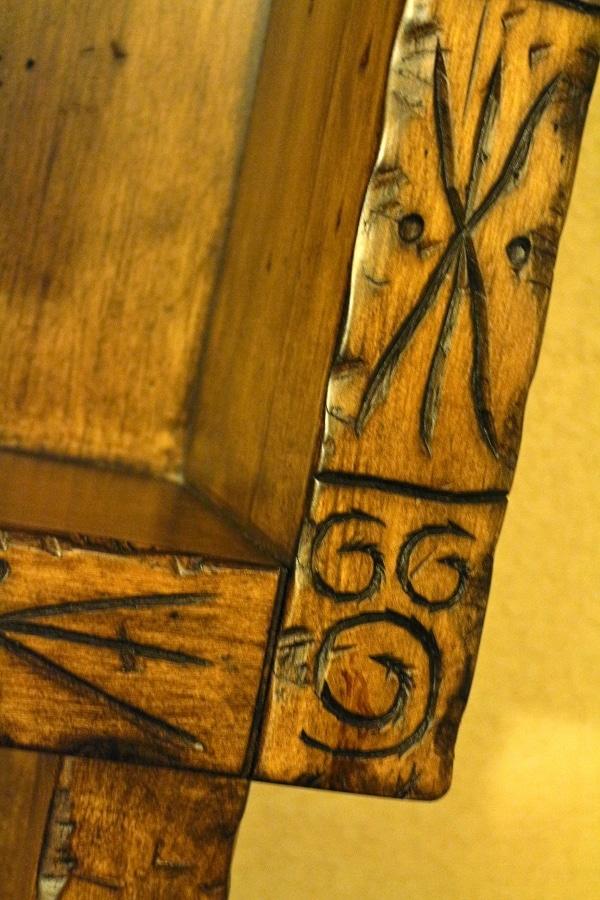 a closeup of a Hidden Mickey carved on a wood dresser
