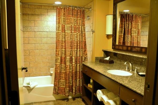 a hotel bathroom with a tub, sink and mirror