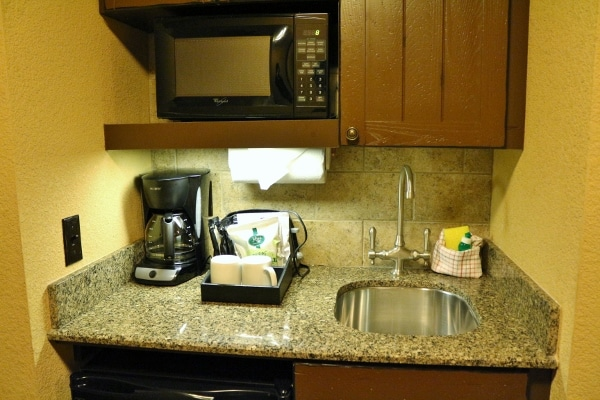 A kitchenette with a sink, coffee maker, and microwave