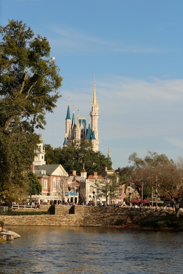 a wide view of Cinderella Castle with a body of water in the foreground