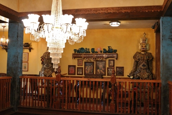 a crystal chandelier hanging in front of various Asian decorations against a wall