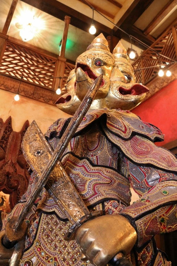 a statue of an Asian warrior with a golden head and big swords
