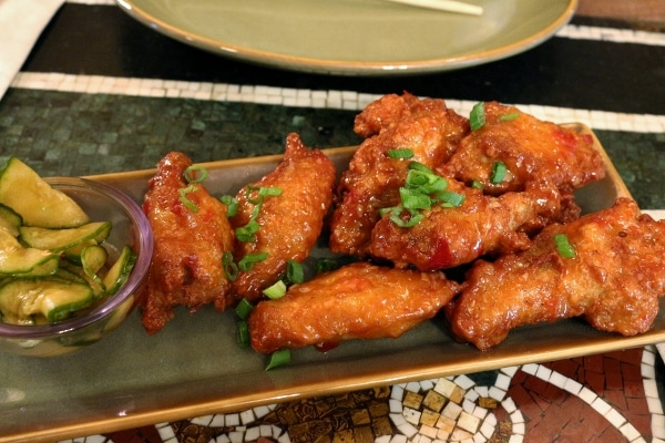 A plate of fried chicken wings garnished with scallions