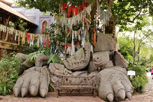 a stone sculpture, bench, and hanging fabrics beneath a tree