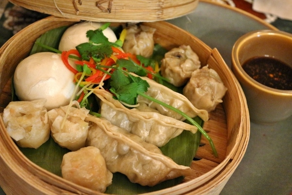 A bamboo steamer basket filled with a variety of Asian dumplings