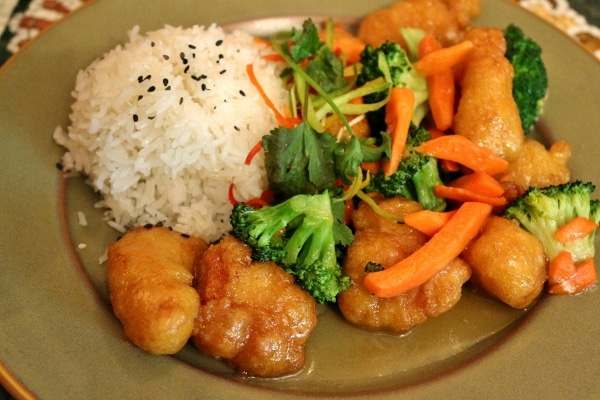 A plate of crispy honey chicken with broccoli and carrots, and a scoop of white rice