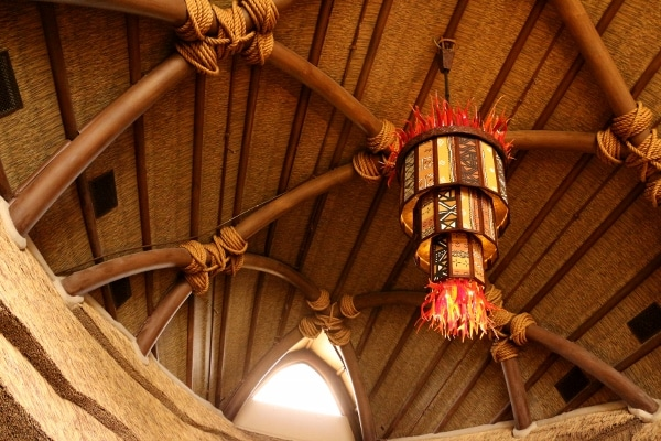 view looking up at the thatched ceiling and colorful lights inside the Animal Kingdom Villas lobby