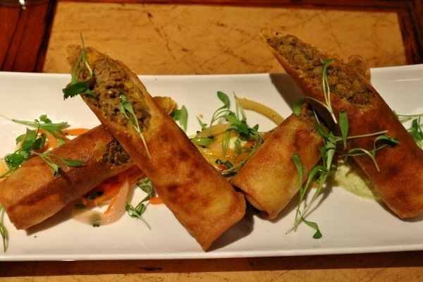 two crispy spring rolls cut in half and arranged artfully on a white plate
