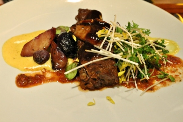 A plate of beef short ribs with mushrooms and greens