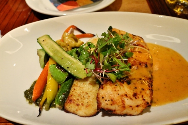 A plate of fish served with vegetables and microgreens on top