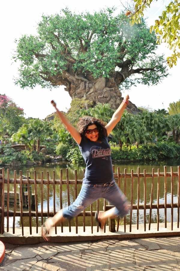 A woman jumping in front of the Tree of Life in Disney\'s Animal Kingdom park