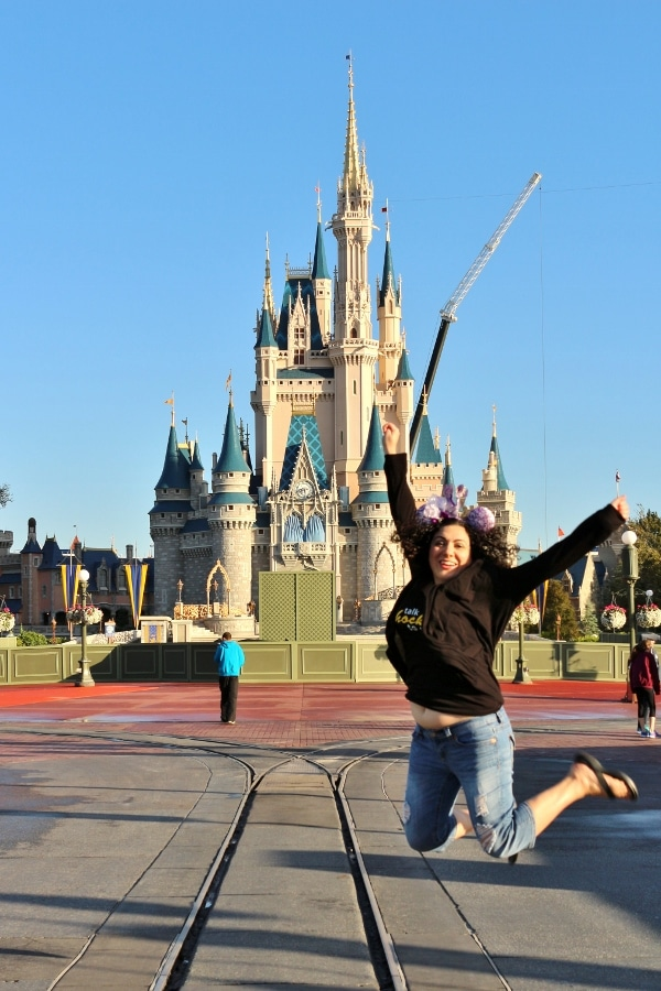a woman jumping in front of Cinderella\'s Castle in the Magic Kingdom