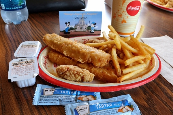 A plate of fried fish and chicken tenders with french fries