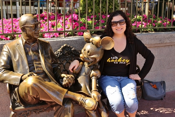 A woman posing on a bench with a statue of Minnie Mouse