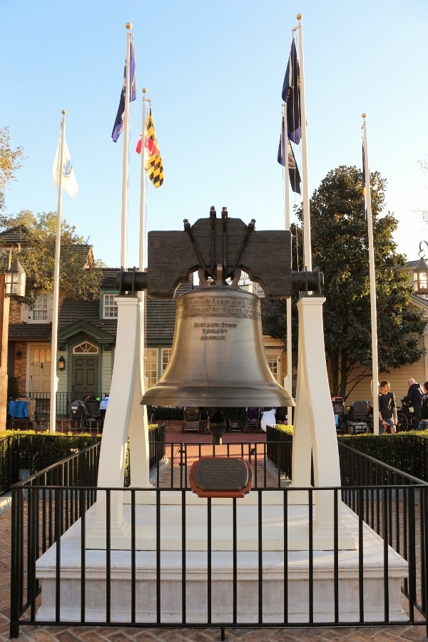 a large bell on display beneath some flags