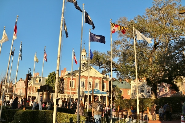 a bunch of flag poles with flags in front of a brick building
