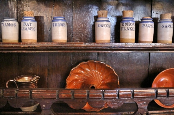 old-fashioned looking dishes and spice containers on shelves