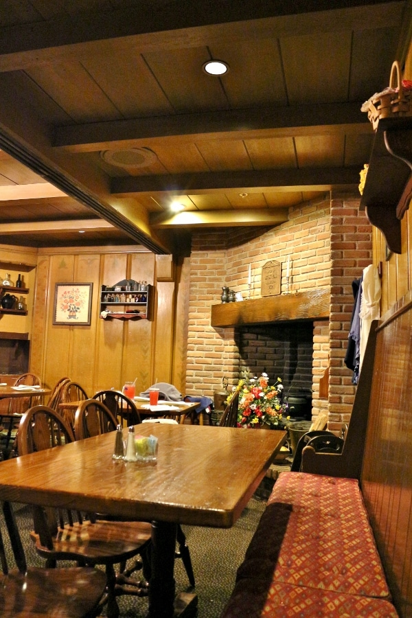 a cozy restaurant dining room with a brick fireplace and wooden tables
