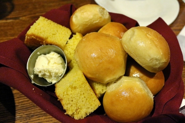 a basket of bread rolls and corn bread with a side of butter