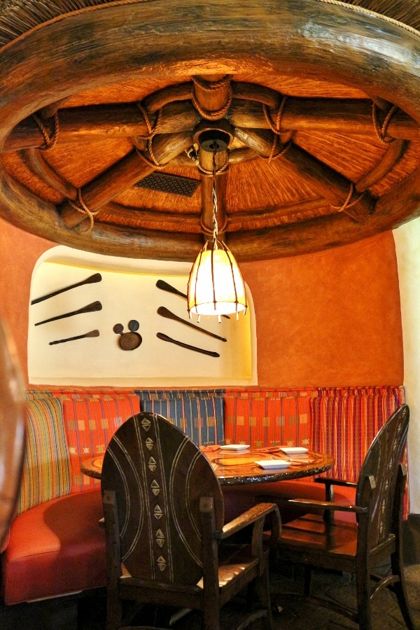 a colorful table in a restaurant with a Hidden Mickey hanging on the wall