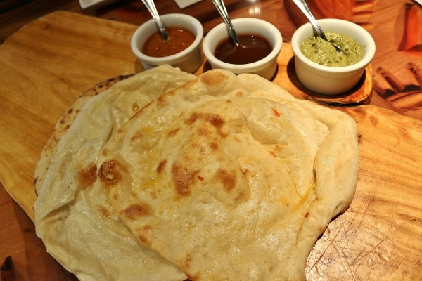 a platter of naan with three dipping sauces on the side