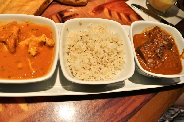 overhead view of two types of curry and rice in small white bowls