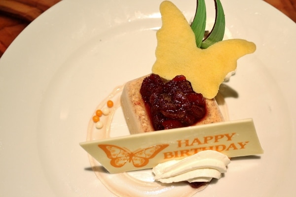 a dessert plate with a sign that says Happy Birthday