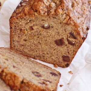 Closeup of a partially sliced loaf of banana date bread.