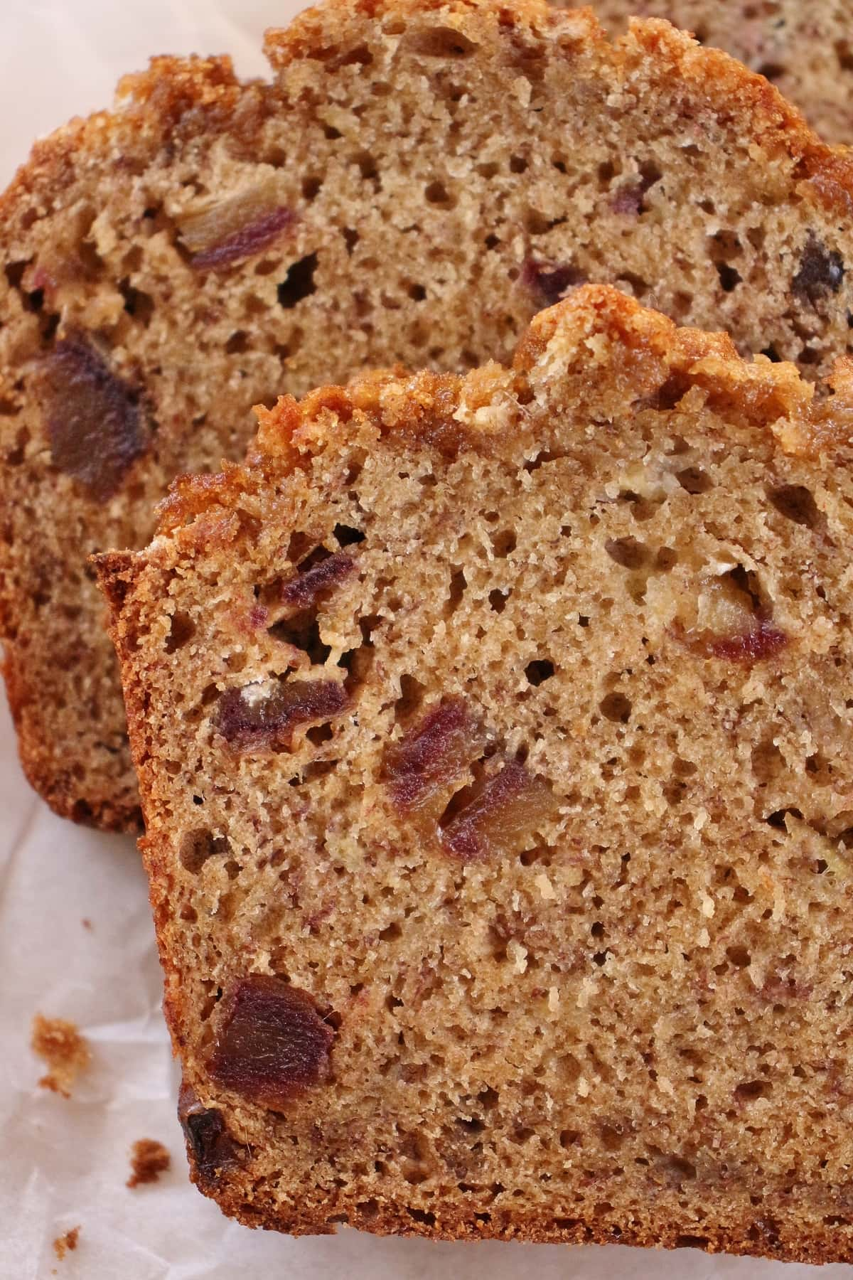 Closeup of slices of banana bread with chopped dates inside.