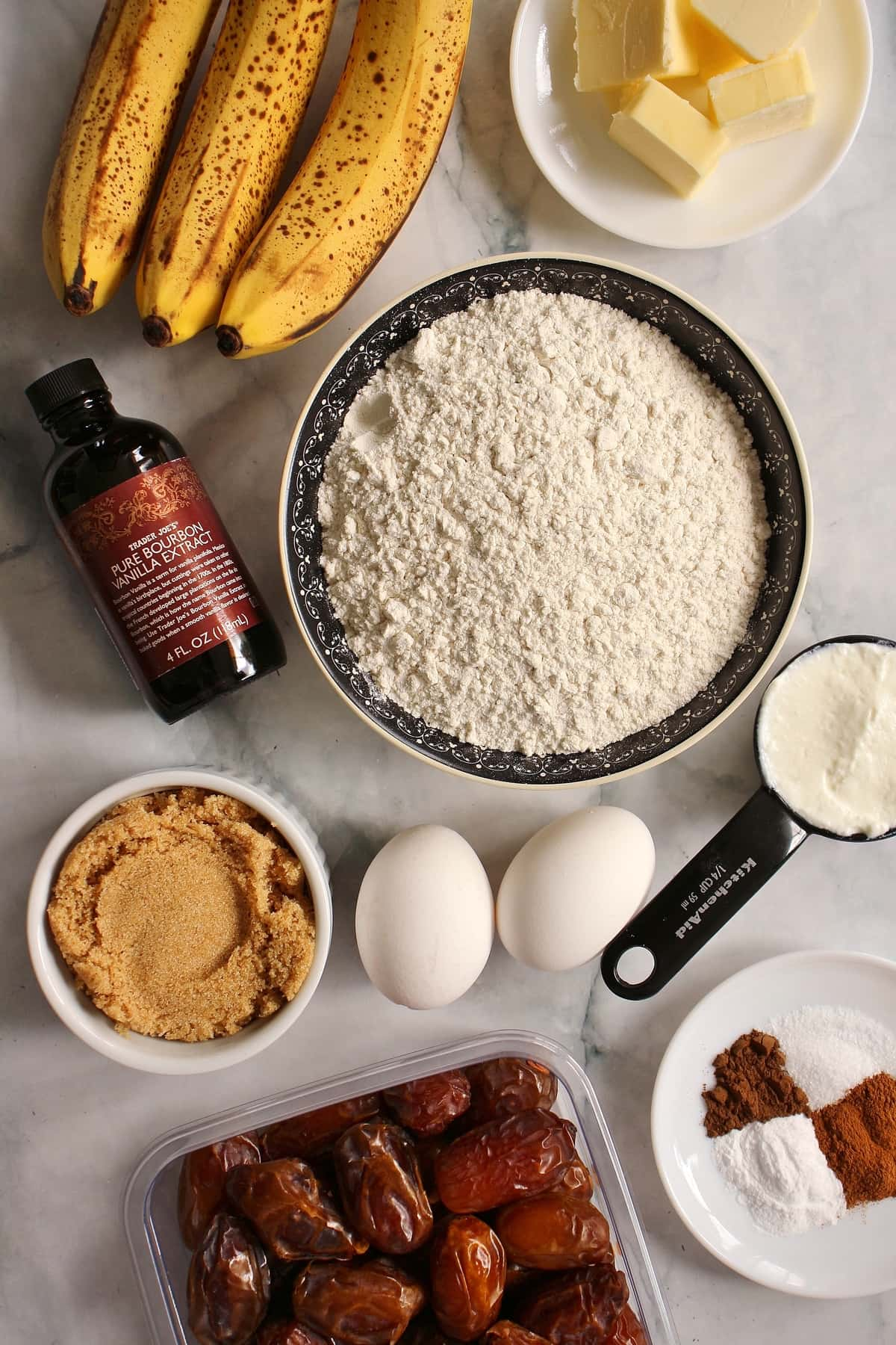 Bananas, a bowl of flour, brown sugar, eggs, dates, and a bottle of vanilla extract.