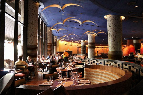 inside a restaurant dining room with a blue ceiling and lights that look like flying birds