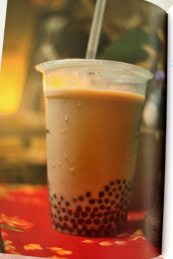 A clear plastic cup of bubble tea with a straw