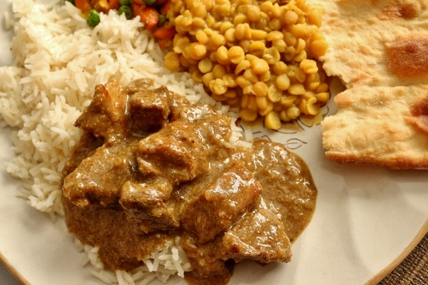 a closeup of pork vindaloo served over white rice on a plate with other Indian dishes