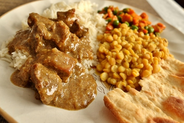 side view of a plate of food including pork vindaloo served over white rice