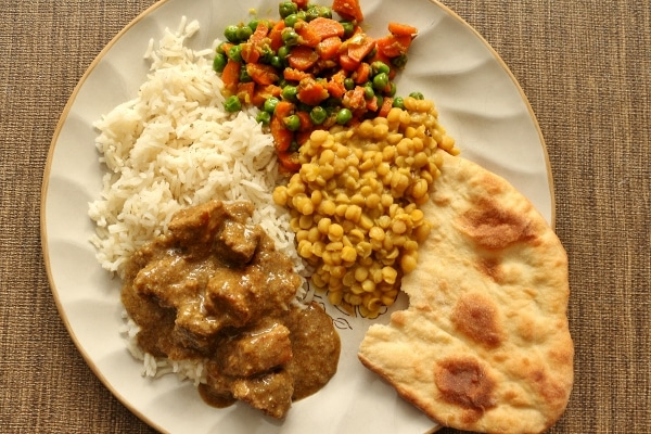 A plate of Indian food including white rice, pork vindaloo, naan bread, chana dal, and vegetables