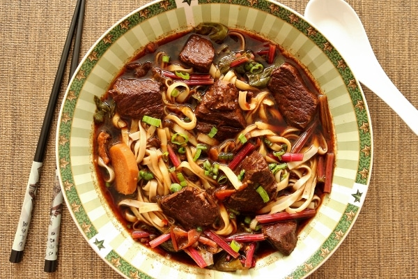 overhead view of a bowl of beef noodle soup with chopsticks on the side