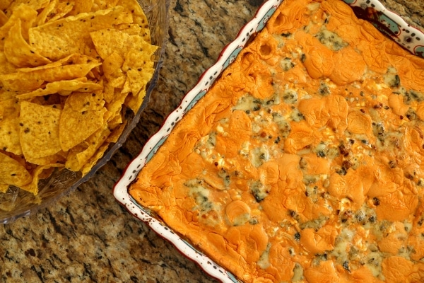 overhead view of a square baking dish of buffalo chicken dip with chips on the side