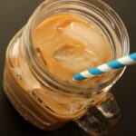 Cold-brewed iced coffee in a mason jar mug with a blue and white striped paper straw