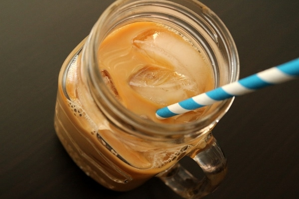 Cold brew iced coffee in a mason jar mug with a blue and white striped paper straw