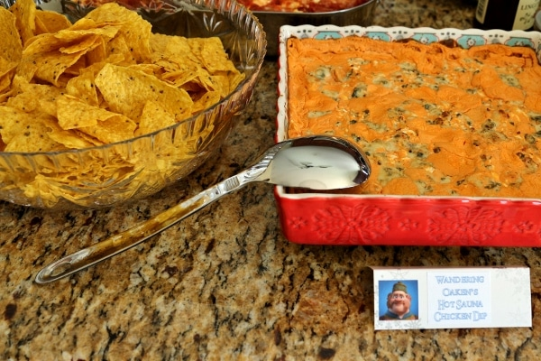 a bowl of tortilla chips and a square baking dish of buffalo chicken dip