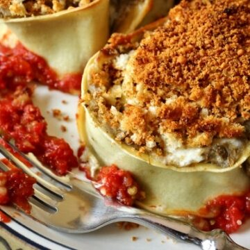 a closeup of an eggplant rotolo topped with bread crumbs on a plate with a fork