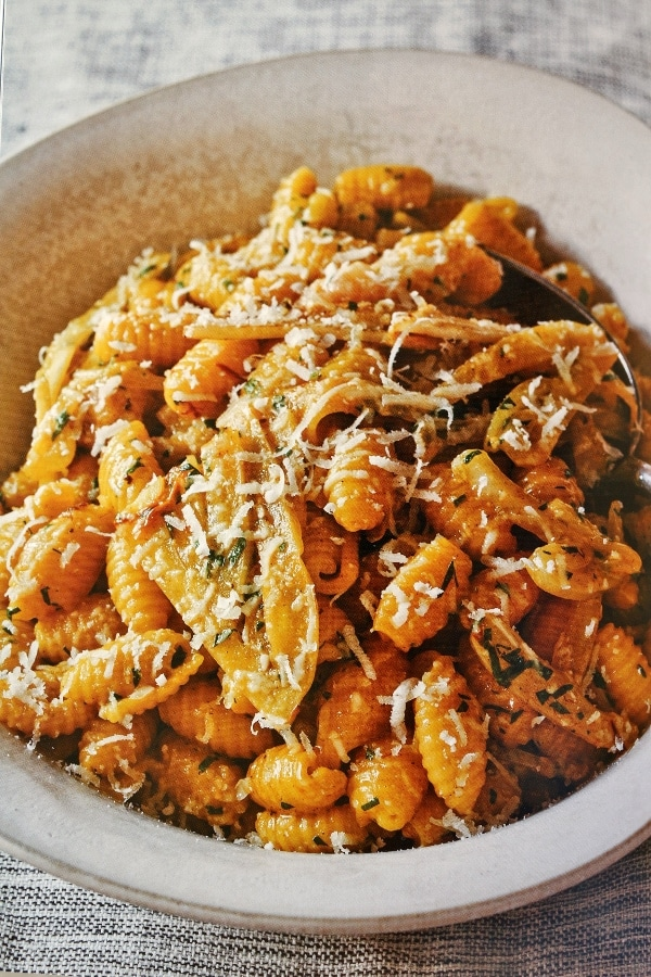 A bowl of cavatelli pasta topped with grated cheese