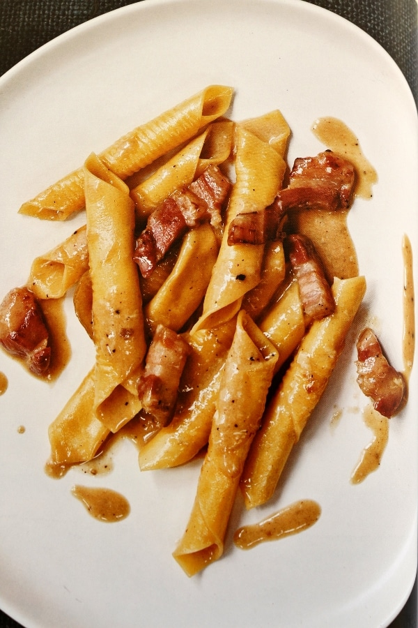overhead view of garganelli pasta with bacon on a white plate