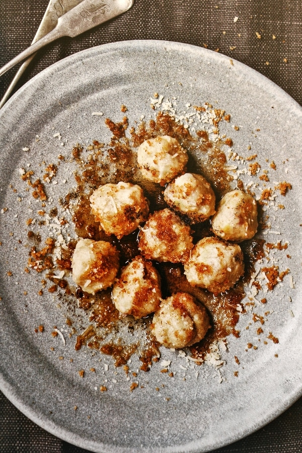a plate of round gnocchi topped with bread crumbs