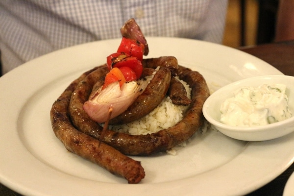 a long piece of merguez sausage served over rice on a plate