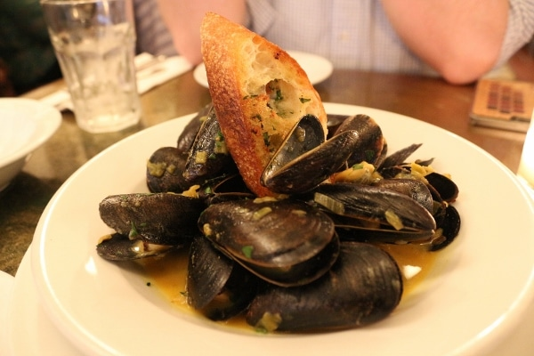 A plate of mussels topped with a piece of crusty bread