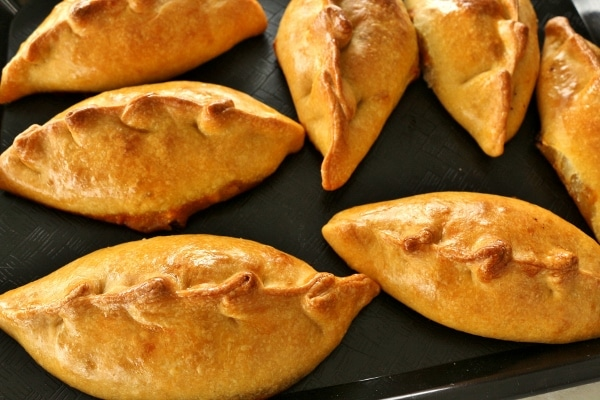 shiny golden brown saltenas empanadas arranged on a black tray