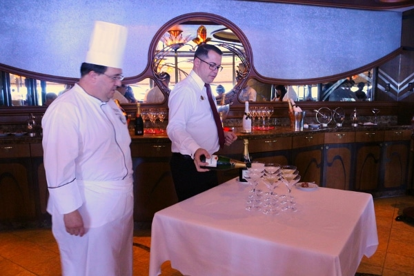 a man standing at a table next to a chef pouring glasses of Champagne